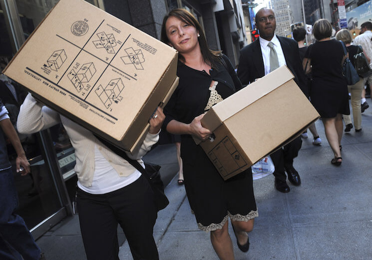Women carrying boxes leave the Lehman Brothers headquarters, September 15, 2008, in New York on the day the firm filed for bankruptcy. The largest filing in American history, the Lehman Brothers' bankruptcy unleashed turmoil throughout the global economy. (AP Photo/ Louis Lanzano)