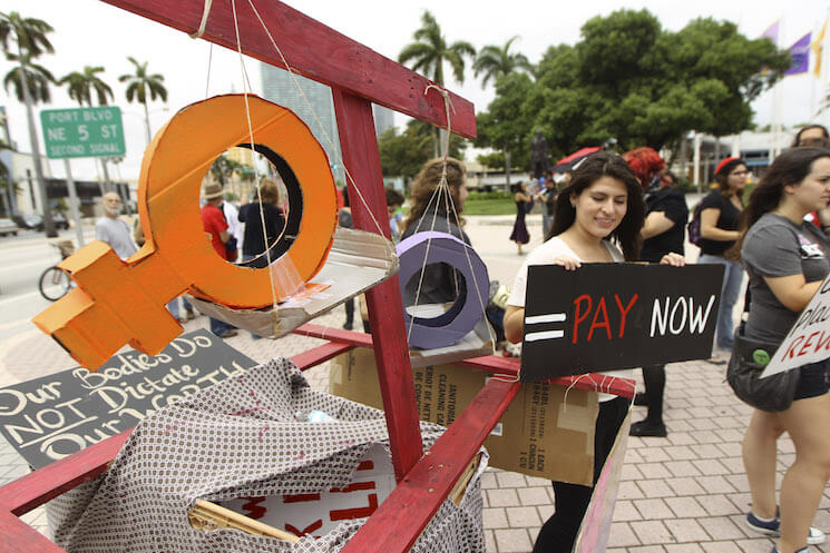 Several women stage a protest in downtown Miami demanding equal pay for women.