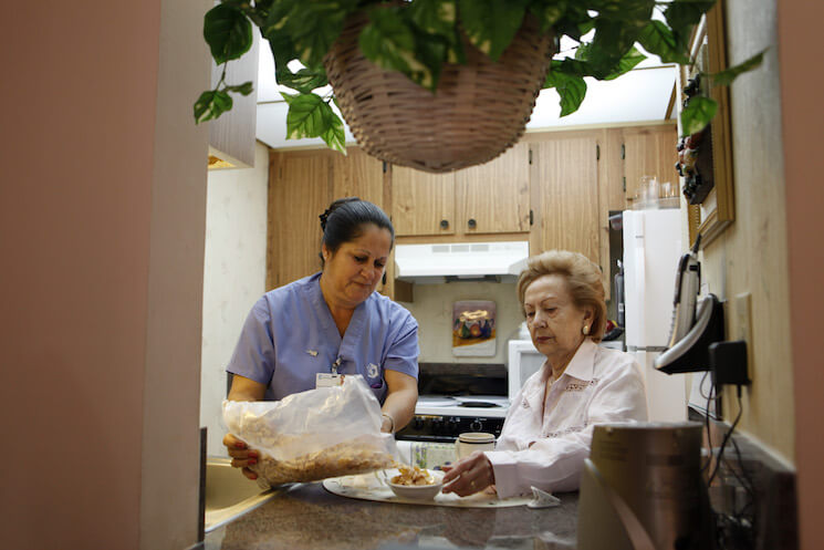 Home health aide Maria Fernandez, left, pours cereal for Herminia Vega, 83, right, as she performs household chores for Vega and her husband.