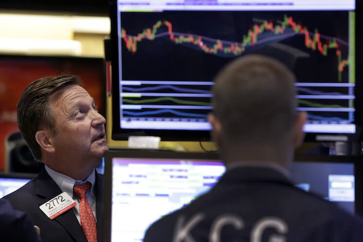 Two traders watch the monitorson the floor ofthe New York Stock Exchange.