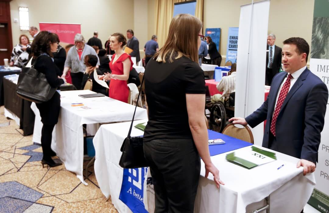 Companies speak with job seekers at a job fair in Pittsburgh, Wednesday, March 30, 2016.