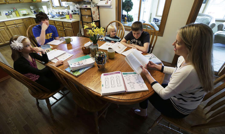 Sara Gustoff, right, reads to her children Abigail, from left, Nathanael, Benjamin, and Jonah while at the kitchen table in their home in Des Moines, Iowa.