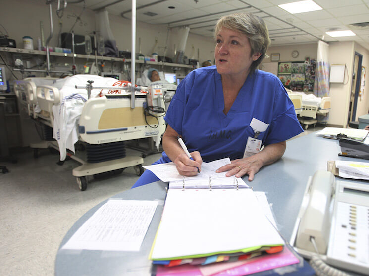 Nurse Mary Pitman checks a patient's chart at the Indian River Memorial Hospital recovery room in Vero Beach, Fla.