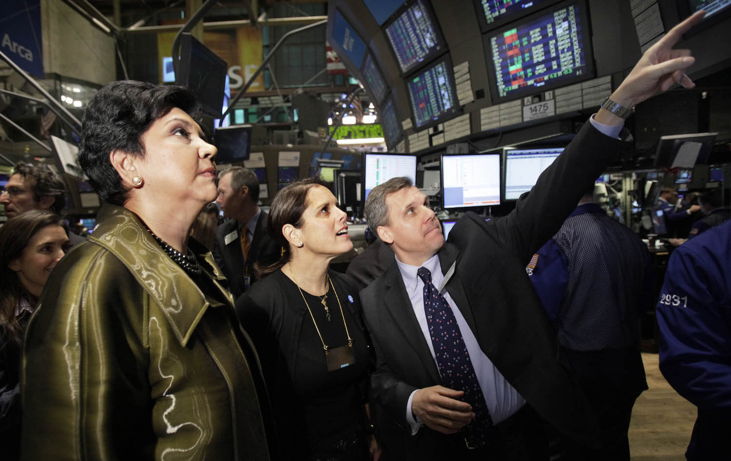 PepsiCo Inc. chairman and chief executive Indra K. Nooyi, left, and Jill Beraud, PepsiCo president of sparkling brands, meet with Barclays Capital investor relations representative Carmen Barone, right, at the post that trades Pepsi on the floor of the New York Stock Exchange Monday, Feb. 1, 2010. (AP Photo/Richard Drew)