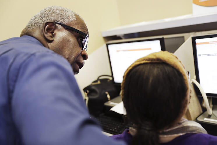 In this Thursday, March 3, 2016, photo, Georgia Department of Labor services specialist Louis Holliday, left, helps a woman with a job search at an unemployment office in Atlanta.