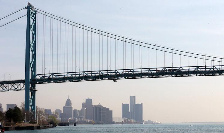 The Detroit skyline is seen under the Ambassador Bridge.