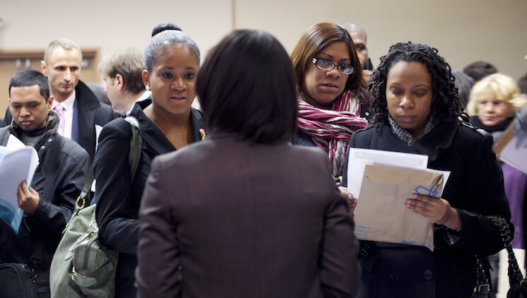 People talk with a recruiter, center, at a job fair sponsored by National Career Fairs, in New York.