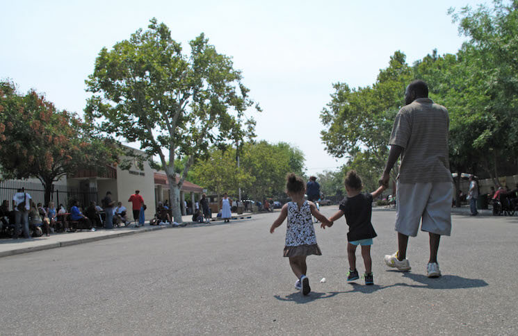 A man walks with two children in Fresno, Calif.