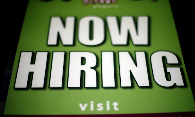 """A """"Now Hiring"""" sign appears in a storefront display window in Philadelphia."""