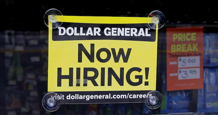 """A """"Now Hiring"""" sign hangs in the window of a Dollar General."""