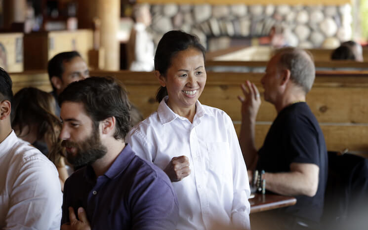 A server smiles as she talks with customers at a Seattle restaurant.