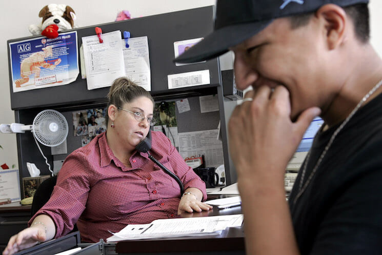 Ayesha Tully, left, responds to call while Larryll Emerson, 20, waits for information pertaining to his next work assignment at the Staffmark temp agency in Cypress, Calif.