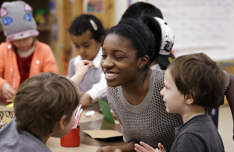 In this photo, assistant teacher D'onna Hartman smiles as she works with children at the Creative Kids Learning Center in Seattle.