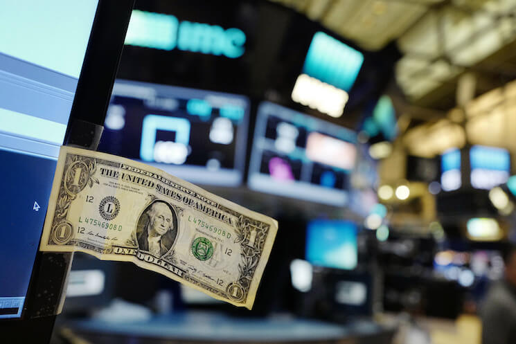 A stock trader has taped a one dollar bill to his computer screen at the New York Stock Exchange.