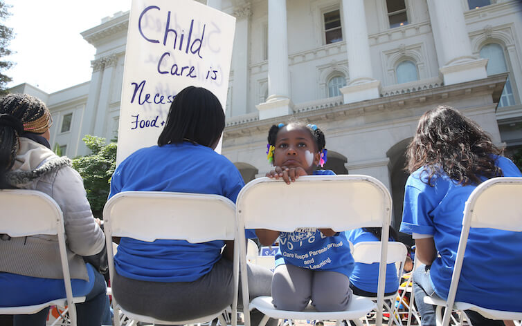 Saryah Mitchell, sits with her mother, Teisa, Gay, left, a rally in Sacramento, Calif.