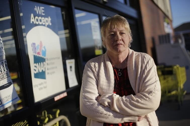 Terry Work stands outside a store that accepts food stamps in Tennessee. Work's 27-year-old deaf son recently was denied disability payments.