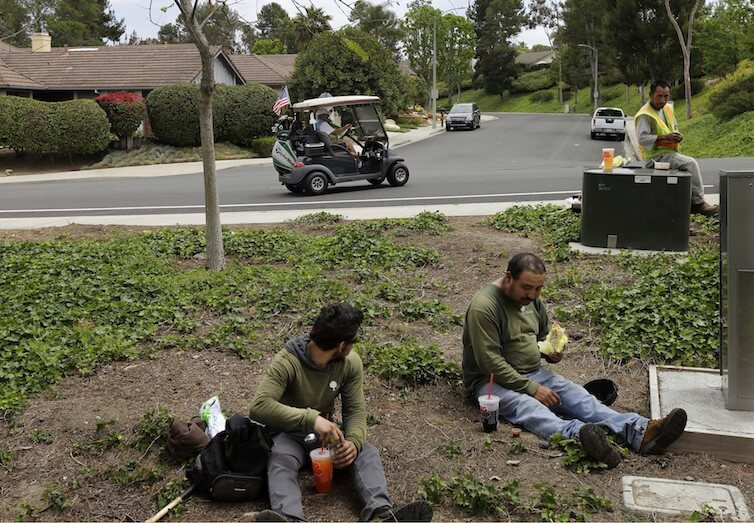 A man drives a golf cart from his house to his golf club as a group of landscape workers take a break in Vista, California.