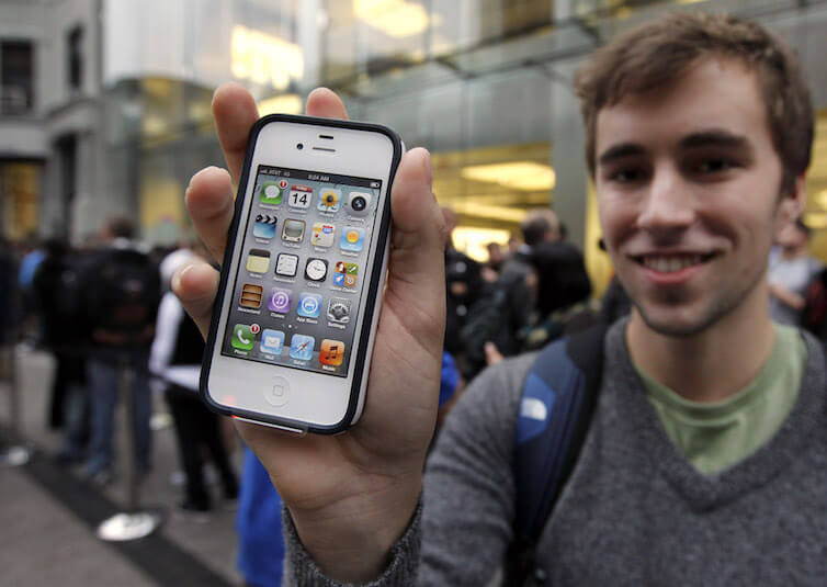 Elliott Johns, of Boston, holds up an iPhone 4S in front of an Apple Store location in Boston.