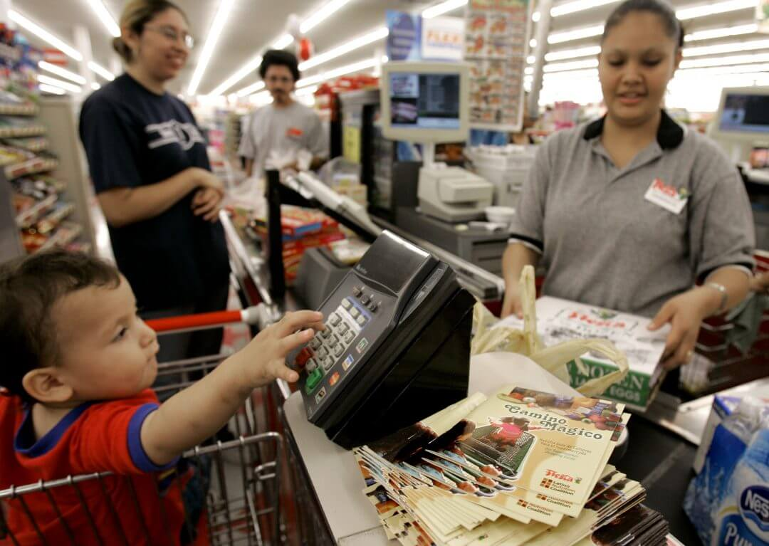 A clerk checks out a customer's groceries at a grocery store in Houston, May 2007.