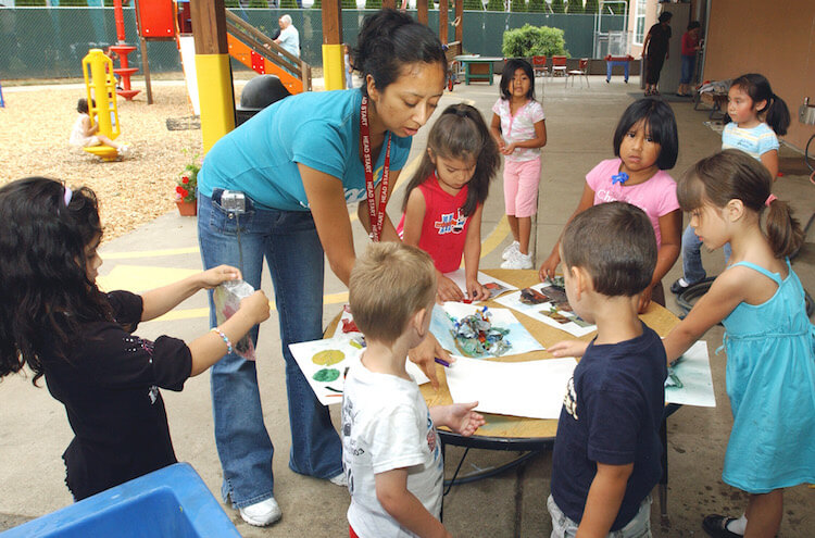 Teacher Margarita Hernandez, second left, leads a group of preschoolers with an outdoor art project at a Head Start Program in Hillsboro, Ore.