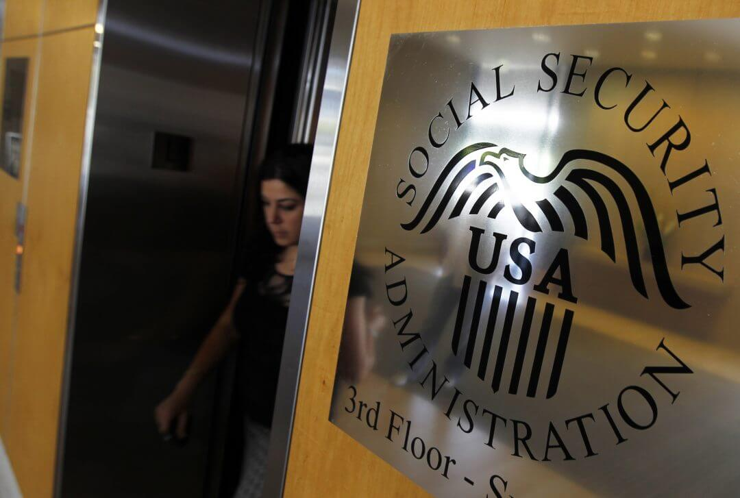 A woman walks past a sign for the Social Security Administration in Los Angeles, July 2011.