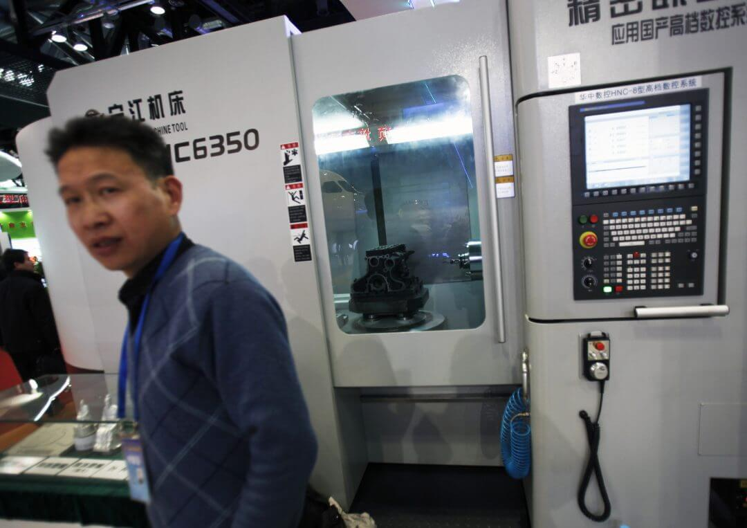 An exhibitor stands near a tool machine on display at an exhibition featuring the science and technology achievement in China at the National Convention Center in Beijing, March 7, 2011.