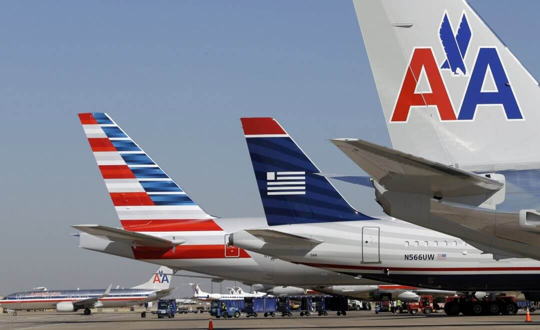 US Airways and American Airlines planes are shown at gates at Dallas/Fort Worth International Airport, February 14, 2013, in Grapevine, Texas.