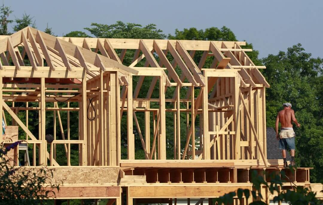 A worker stands in the early morning sunlight on a home construction project in Newtown, Pennsylvania, June 2012.