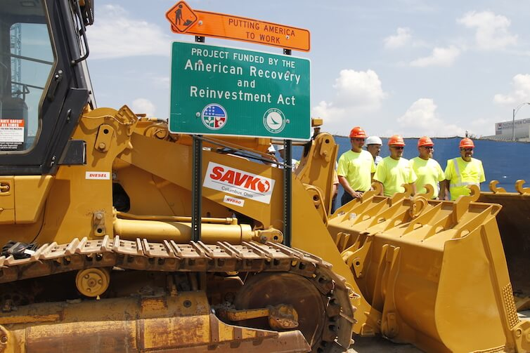 Construction workers look at a highway road project funded by the American Recovery and Reinvestment Act in Columbus, Ohio.