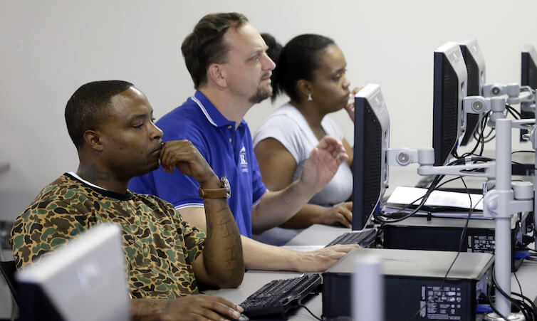 Job seekers look at a computer screens during a resume writing class.