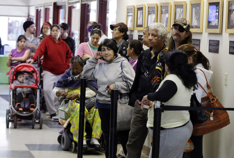 People line up at a food pantry at Sacred Heart Community Service in San Jose, CA.