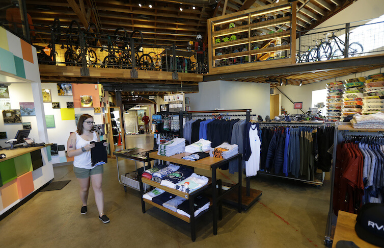 A retail employee folds shirts for display on the main-floor area of a Seattle-based outdoor, bike, ski, and clothing company.