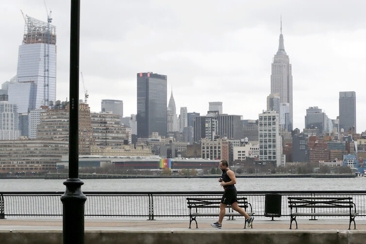 The New York City skyline gives backdrop to a man jogging along the Hudson River in Hoboken, N.J. A new study confirms the correlation between good health and higher socioeconomic outcomes.