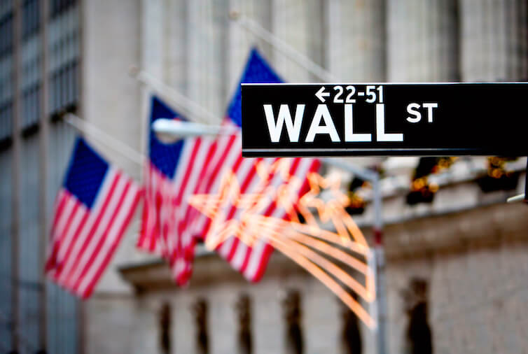 Wall Street sign, with the New York Stock Exchange in the background. A new working paper studies the benefits to businesses of lobbying by looking at the participation of financial institutions in the rulemaking process after the enactment of Dodd-Frank.