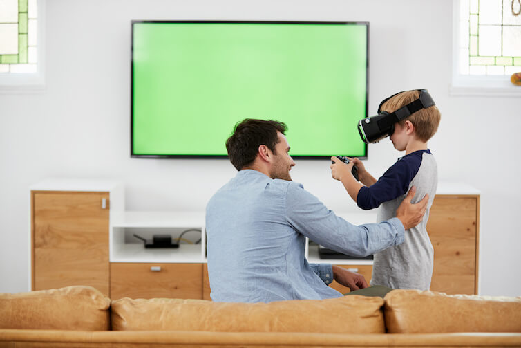 A father and son play with a virtual reality headset. A new study shows thatsons are more likely to start their own businesses if their fathers are entrepreneurial.