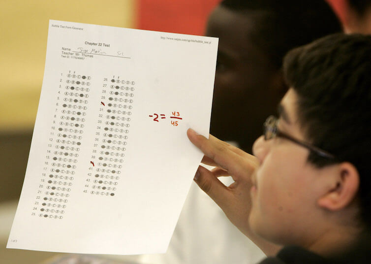 A KIPP charter school student holds up a practice test during class in Houston.