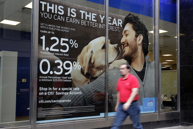 A sign in the window of a Citibank branch in New York shows savings account rates. Secular stagnation, or the consequences of an economy with a long-term excess supply of desired savings over desired investment, requires new macroeconomic solutions that will help alleviate negative effects during the next economic downturn.