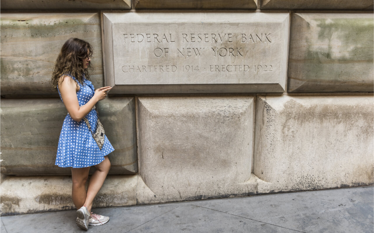 New York, USA – June 18, 2016: A young woman checks her phone in front of the Federal Reserve Bank of New York.