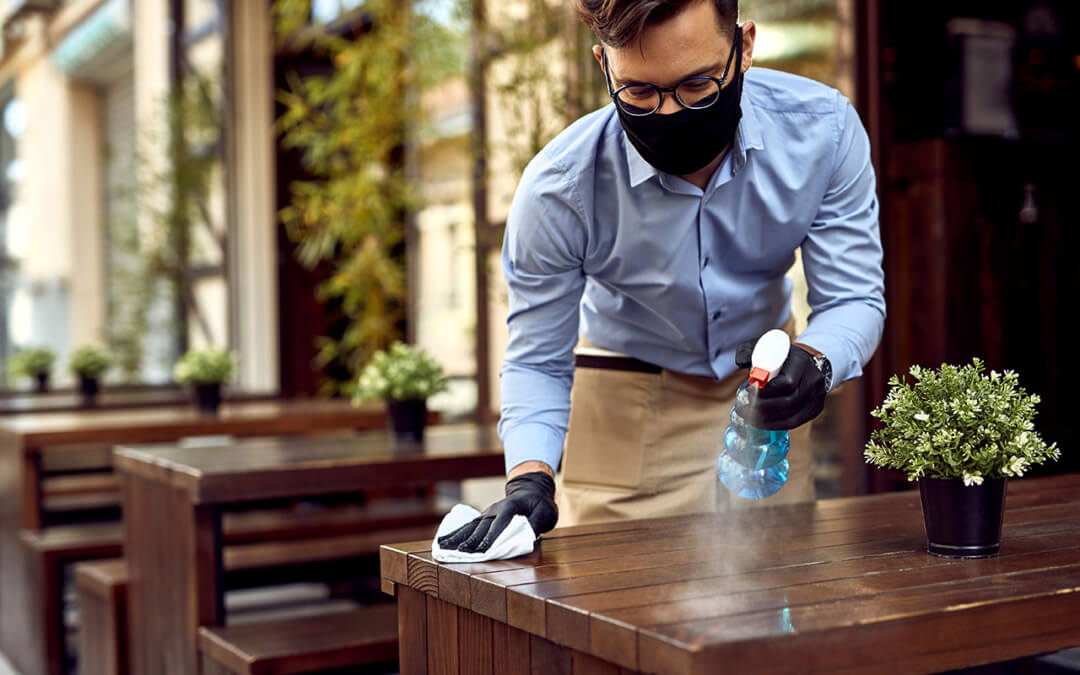A waiter disinfects tables at an outdoor café during the coronavirus pandemic.